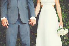 Pares de la boda que llevan a cabo las manos, cierre encima del detalle Fotografía de archivo