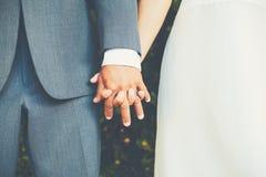 Pares de la boda que llevan a cabo las manos, cierre encima del detalle Fotos de archivo