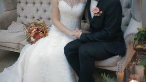 Pares de la boda que llevan a cabo las manos, el novio feliz y la sentada interior de la novia en un sofá Pares jovenes en novia  almacen de video