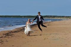 Pares de la boda que saltan en la playa. Foto de archivo libre de regalías