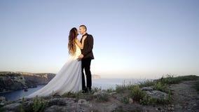 Pares de la boda que se besan en alto cabo superior almacen de metraje de vídeo