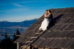 Pares de la boda que se sientan en el tejado de la casa de campo Luna de miel en montañas Foto de archivo