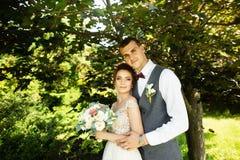 Pares de la boda que sorprenden que presentan en un fondo natural verde fotografía de archivo libre de regalías