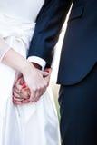 Pares de la boda que sostienen ascendente cercano de las manos Fotografía de archivo libre de regalías