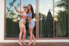 Pares de la chica joven en la terraza que toma la foto de Selfie en el hotel tropical del teléfono elegante de la célula, día de  Fotos de archivo libres de regalías