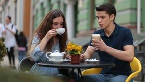 Pares de la datación que se relajan junto en café de la calle metrajes