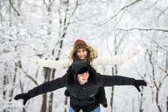 Pares de la diversión del invierno juguetones junto durante vacaciones de las vacaciones de invierno afuera en bosque de la nieve Fotos de archivo libres de regalías