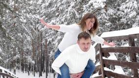 Pares de la diversión del invierno juguetones junto durante vacaciones de las vacaciones de invierno afuera en bosque de la nieve metrajes