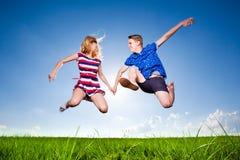 Pares de la diversión en salto en el fondo al aire libre Foto de archivo libre de regalías