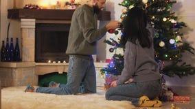 Pares de la diversión que adornan el árbol de navidad en casa Los pares felices se preparan para la fiesta de Navidad Concepto de metrajes