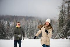 Pares de la diversión que juegan en la nieve, corriendo Imagen de archivo