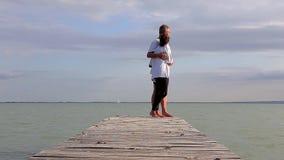 Pares de la Edad Media en el embarcadero en un lago Balatón de Hungría en el verano metrajes