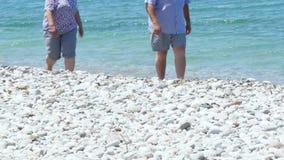 Pares de la Edad Media que caminan cerca del mar Mediterráneo claro en la playa blanca de la piedra de la arena metrajes