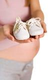 Pares de la explotación agrícola de la mujer embarazada de zapatos blancos Imagenes de archivo