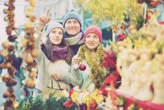 Pares de la familia con la chica joven que elige la decoración de la Navidad Imagen de archivo
