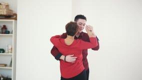 Pares de la familia - el varón y la hembra está bailando kizomba en el estudio blanco cerca de ventana almacen de video