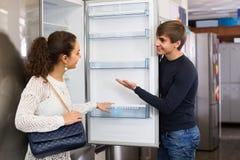 Pares de la familia que eligen el nuevo refrigerador en hipermercado imagen de archivo