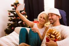 Pares de la feliz Navidad que hacen las fotos del uno mismo en casa imágenes de archivo libres de regalías