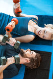 Pares de la gente joven de la aptitud que ejercita con pesas de gimnasia Imagenes de archivo