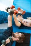 Pares de la gente joven de la aptitud que ejercita con pesas de gimnasia Foto de archivo libre de regalías