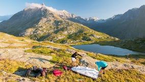 Pares de la gente que pone una tienda de campaña en las montañas, lapso de tiempo Aventuras en las montañas, el pico majestuoso y almacen de video
