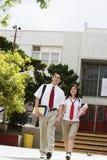Pares de la High School secundaria que caminan delante de escuela Fotografía de archivo