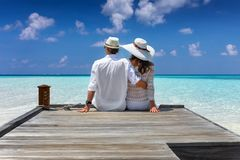 Pares de la luna de miel que abrazan en un embarcadero de madera en las islas de Maldivas foto de archivo