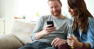 Pares de la moda de los jóvenes de los amantes que juegan con el móvil Imágenes de archivo libres de regalías