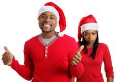 Pares de la Navidad del afroamericano con los sombreros de santa Imagen de archivo libre de regalías