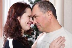 Pares de la Navidad Familia sonriente feliz en casa que celebra Gente del Año Nuevo Imagen de archivo libre de regalías