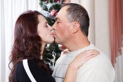 Pares de la Navidad Familia sonriente feliz en casa que celebra Gente del Año Nuevo Foto de archivo