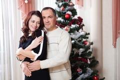 Pares de la Navidad Familia sonriente feliz en casa que celebra Gente del Año Nuevo Imagenes de archivo