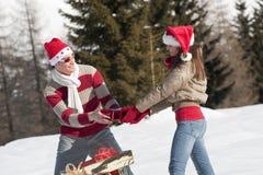 Pares de la Navidad que juegan con los regalos en la nieve Fotos de archivo libres de regalías
