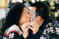 Pares de la Navidad que sostienen el palillo del caramelo imagen de archivo libre de regalías
