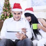Pares de la Navidad usando la tableta digital a hacer compras en línea Imagen de archivo