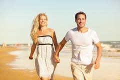 Pares de la playa que llevan a cabo las manos que corren divirtiéndose imagen de archivo