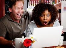 Pares de la raza mezclada en café con los comp de la computadora portátil Fotos de archivo