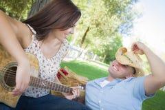 Pares de la raza mixta de la diversión con la guitarra y el vaquero Hat en parque Foto de archivo