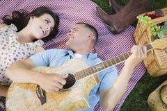 Pares de la raza mixta de la diversión que tocan la guitarra y que cantan Imagen de archivo
