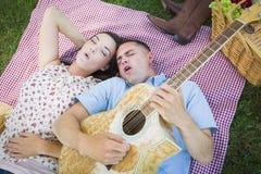 Pares de la raza mixta en el parque que toca la guitarra y que canta Imagen de archivo libre de regalías