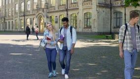 Pares de la raza mixta de los estudiantes que caminan en el patio de la universidad después de clases almacen de video