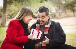 Pares de la raza mixta que comparten la Navidad o el regalo del día de tarjetas del día de San Valentín Fotos de archivo libres de regalías