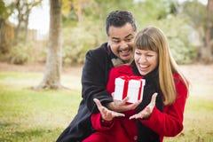 Pares de la raza mixta que comparten la Navidad o los regalos del día de tarjetas del día de San Valentín Foto de archivo