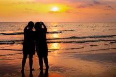 Pares de la silueta en el fondo de la puesta del sol de la playa imagenes de archivo