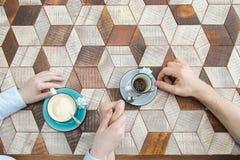 Pares de la visión superior que se sostienen por las manos que beben el café Fotografía de archivo libre de regalías