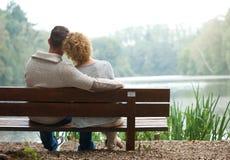 Pares de la vista posterior que se sientan en banco al aire libre Fotografía de archivo
