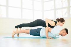 Pares de la yoga, hombre y mujer, ejercicios de práctica en un pasillo del entrenamiento Foto de archivo libre de regalías