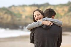 Pares de las adolescencias que abrazan en la playa imagen de archivo