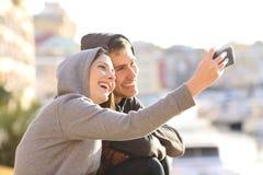 Pares de las adolescencias que toman un selfie al aire libre Imágenes de archivo libres de regalías