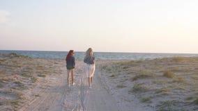 Pares de las mujeres jovenes que caminan la playa arenosa en el traje de baño y los pantalones cortos del estilo del boho del ind almacen de video